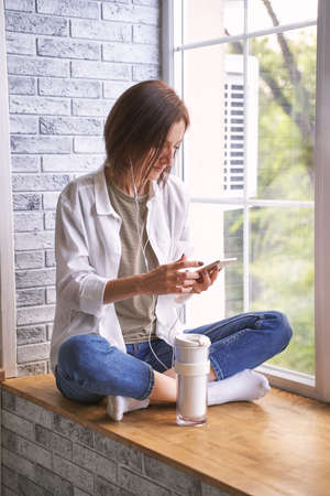 Young woman sitting at windowsill. Working on phone. Online study concept. Safety lockdown distance teaching. Female person. Quarantine office. Business writer. Plat game Фото со стока