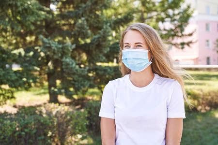 Young woman wearing protective mask outdoors. Medicine equipment. Pandemic safety concept. White t-shirt. Sick allergy or dust. Фото со стока