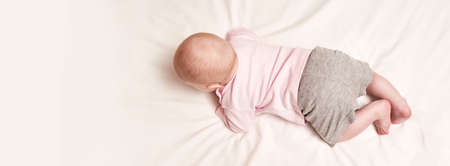 Cute small boy lying at bed. Back view. Body concept. Light background. Serious child. Copyspace. Stay home. Mockup. Horizontal banner. Pink female clothes