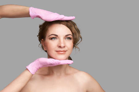 Doctor hands in protective medical gloves. Derma test. Prepare operation consultation. Pretty young woman. Face treatment. Blepharoplasty or rhinoplasty clinic. Cosmetology concept