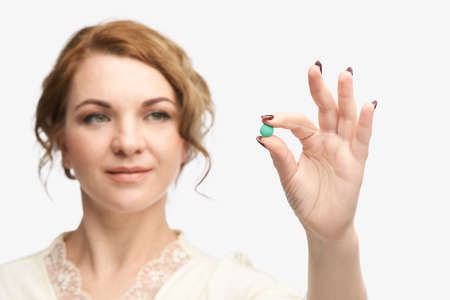 Girl holding a pill. Vitamins concept. Beautiful portrait on white background. Medicine home routine. Female morning supplement. Meds anti allergy drug Фото со стока