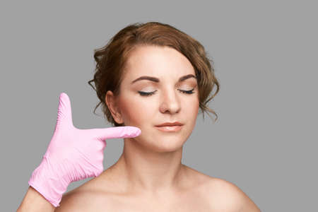 Facial spa treatment. Dermatology spa mask. Detox therapy. Rejuvenation skincare beauty. Girl finger point on face. Health cosmetology concept. Grey background. Copyspace, banner. Show lips