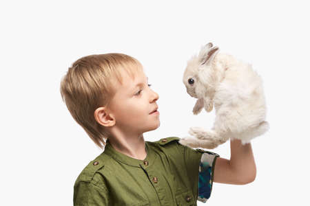 Little pretty boy holding fur rabbit baby. White cute pet at studio. Happy easter hug. Male person hand. Young people.