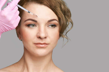 Face needle injection. Young woman cosmetology procedure. Doctor hand in glove holds. Female patient