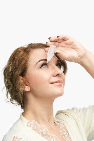 Woman using eye drops. Medicine treatment. Eyecare human problem. Ophtalmology dropper. Фото со стока