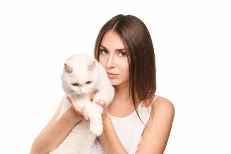 Young woman holding white cat. Allergy concept. Pretty animal. Lifestyle. Human and pet