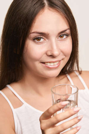 Girl drink water on white background. People lifestyle concept. Beauty fashion model. Business. Morning fitness. Body care Фото со стока