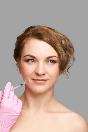Lips injection at spa salon. Doctor hands. Pretty female patient. Beauty treatment. Healthy skin procedure. Young woman face. Grey background. Plasmolifting rejuvenation. Dermatology mask Фото со стока