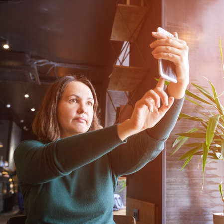 Young woman doing self portrait at cafe. Blogger selfie video. Happy emotion. Smiling female person. Lifestyle action. Pretty posing. Copyspace