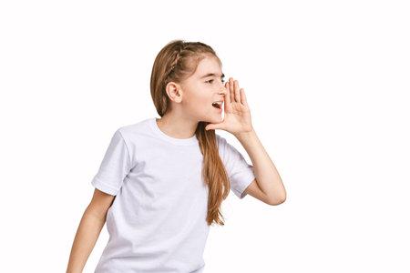 Children portrait in white t-shirt. Studio isolated concept. Shout rumor. Secret gossip. Modern communication. Girl hold hand near head Фото со стока