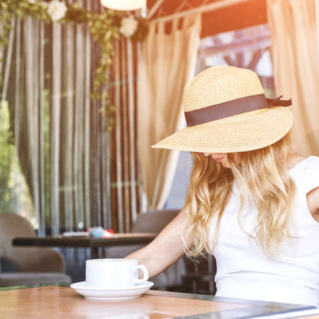 Young woman sitting at street cafe. Staycation tourist. Female person in summer hat. Hiding face. Dreaming about vacation. Inclusive concept