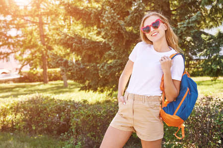 Young woman with bright backpack. Local tourist. Summer sunny day. Green background.Staycation weekend.