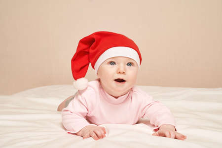 Cute small boy lying at bed. Childhood christmas concept. Light background. Smiling child. Xmas red hat. Copyspace