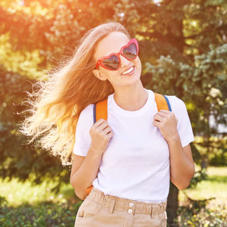 Young woman with bright backpack. Local tourist. Summer sunny day. Green background. Staycation weekend.