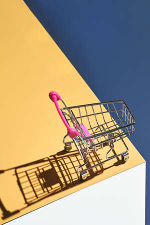 Shop trolley on yellow and blue bright background. Modern mall concept. Isometric trendy layout. Market cart trend wallpaper. Supermarket empty accessory