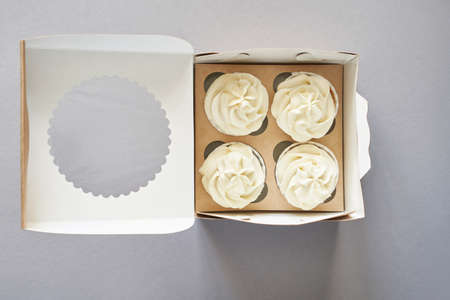 Paper box with cream cupcake. Birthday sweet bakery. Cookies four pack. Yummy buttercream dessert. Wedding party food. Grey background. Holiday recipe 免版税图像