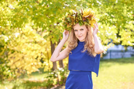 Middle age woman with autumn maple wreath. Yellow and green colors. Backyard nature. Female adul tportrait. Happy people. Model posing at park 版權商用圖片