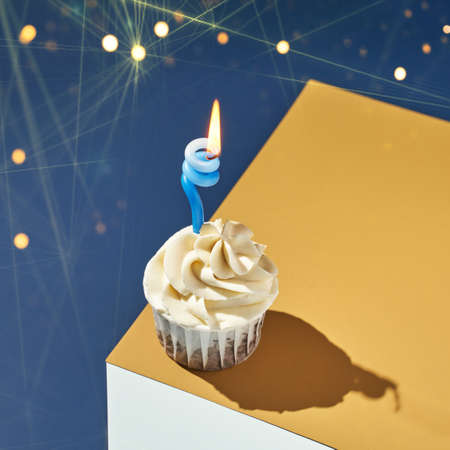 Milky cream cupcake. Birthday sweet bakery. Cookies. Yummy buttercream dessert. Wedding party food. Blue and yellow background. Holiday recipe. Anniversary gourmet. One pieces. Candle light. Bokeh 免版税图像
