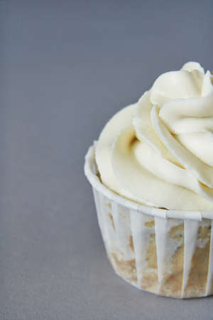 Milky cream cupcake. Birthday sweet bakery. Cookies. Yummy buttercream dessert. Wedding party food. Grey background. Holiday recipe. Anniversary gourmet. Closeup. One piece 免版税图像