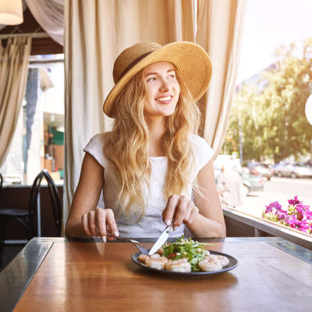 Young woman at restaurant eating shrimp salad. Health food concept. Fork and knife. Ountdoor cafe. Hands near plate. Mediterranean diet meal. Female person in hat