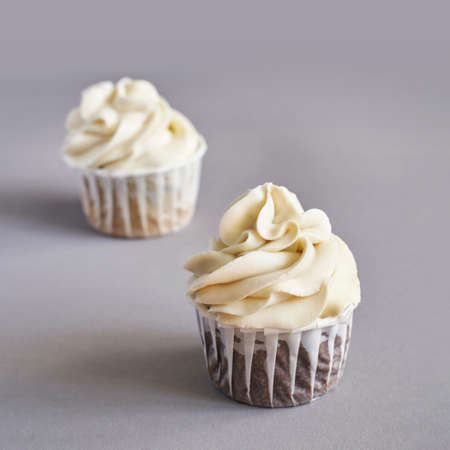 Milky cream cupcake. Birthday sweet bakery. Cookies. Yummy buttercream dessert. Wedding party food. Grey background. Holiday recipe. Anniversary gourmet. Two pieces