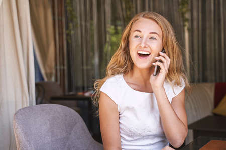 Pretty young woman talking by phone. Happy female person outdoors. Summer business portrait. Lady calling friends or boyfriend. Blonde long hair. Cute adult student at town