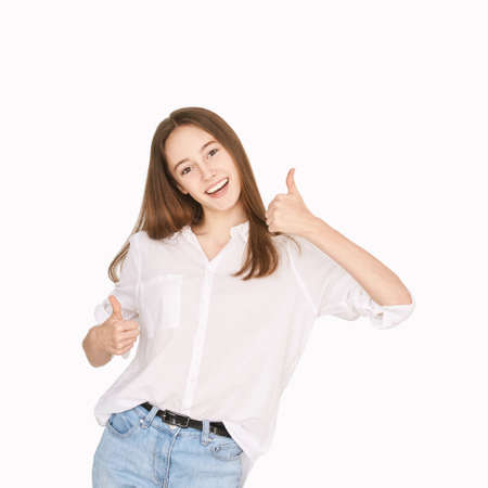 Pretty girl indoor portrait. Light background. Female teenager person. Long brow hair. Happy smile emotion. Thumb up like gesture. Attractive teenager 版權商用圖片