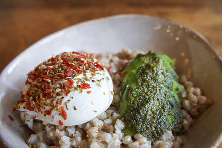 Healthy food at vegan cafe. Green buckwheat with poached egg and avocado. Lifestyle Modern plate with porridge. Cereal breakfast menu