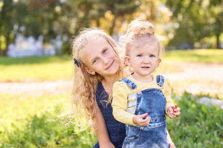 Two little sisters together at park. Family happiness portrait. Female child relationship. Vacation nature friendship. Happy blond. Curly hair. Green color outdoors