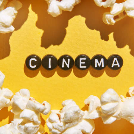 Popcorn quote design. Typography concept. Creative text wallpaper. Phrase yellow background. Cinema food concept. Film delicious snack. Black round letters 免版税图像