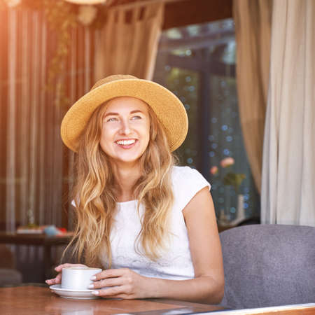Young woman drinking coffee at street cafe. Staycation tourist. Female person in summer hat. Positive emotion. Smiling people. Dreaming about vacation