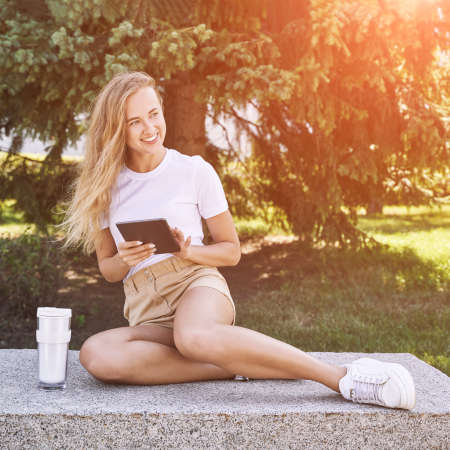Young woman sitting outdoors. Working on tablet. Online study concept. Safety lockdown distance teaching. Female person. Quarantine office. Business writer. Video relax. Copyspace 免版税图像
