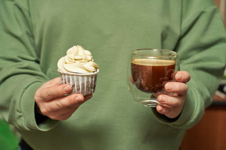 White cream cupcake. Birthday sweet bakery. Cookies. Yummy buttercream dessert. Wedding party food. Green dress background. Holiday recipe. Hand holding with coffee cup