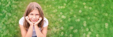 Little girl portrait. Outdoor green background. Looking. Teenager schoolgirl at park. Cute face. Children beauty. Female head. Charisma caucasian