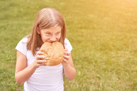 Child holds and bite round bread. Healthy food. Carrying big fresh baker bun. Rustic product. Enjoy warm breakfast. Craft cuisine. Home made lunch. Green outdoor background 版權商用圖片