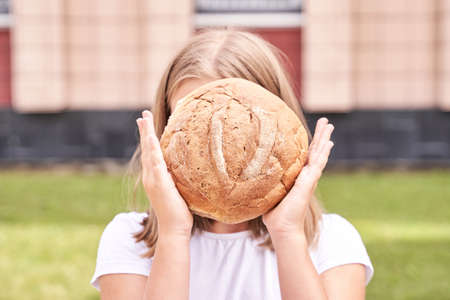 Child holds and bite round bread. Healthy food. Carrying big fresh baker bun. Rustic product. Enjoy warm breakfast. Craft cuisine. Home made lunch. Green outdoor background. Anonymous trend