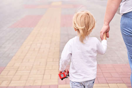 Mother hold sun hand. Outdoor family lifestyle. Mentor concept. Trust assistance. Parent help. Little person touch. Summer. Adult and baby. Toddler person 版權商用圖片