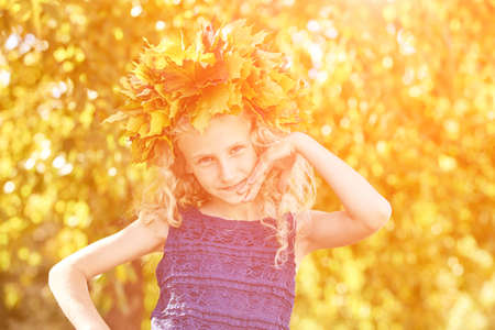 Little girl with autumn maple wreath. Yellow and green colors. Backyard nature. Female child portrait. Happy people. Model posing at park