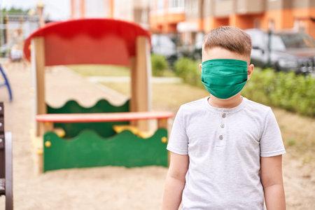 Child in safety mask. New normal. virus safety portrait. Boy. Playground background. Outdoors. Health care Standard-Bild