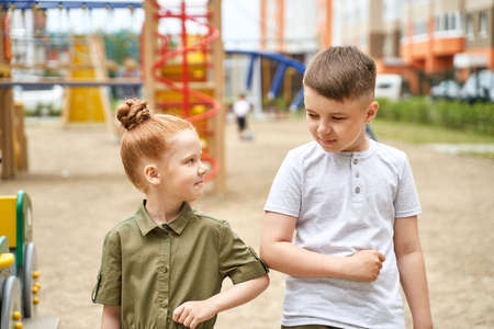 Elbow touch. New normal. virus safety handshake. Boy and girl greeting. Family sign. Arm salute gesture. Playground background. Outdoors. Health care