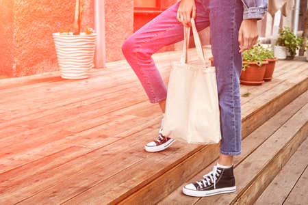 Girl with sustainable bug. Ecology lifestyle concept. Reusable flax shopper. Female person holding textile handbag. Outdoors market.