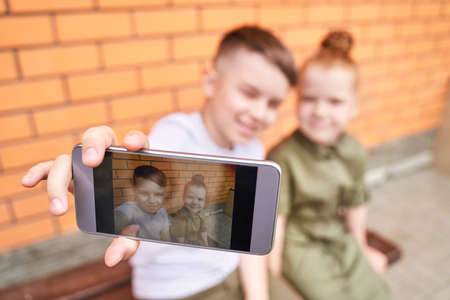 Pretty face. Cute school child taking selfie. Active vacation. Brother and sister. Online video call. Happy children concept. Lifestyle action. Standard-Bild