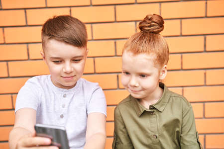 Pretty face. Cute school child taking selfie. Active vacation. Brother and sister. Online video call. Happy children concept. Standard-Bild