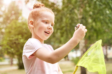 Little girl playing with butterfly net. Summer adventure. Happy toddler. Catch bug scoop.