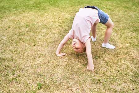 Cute school child doing yoga exercise. Active vacation. Small people in bridge pose. Online video call. Happy children concept. Lifestyle action. Watching sport lesson