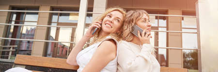 Two pretty young woman talking by phone. Happy female person outdoors. Summer city business portrait. Lady calling friends. Blonde hair. Cute adult student at town