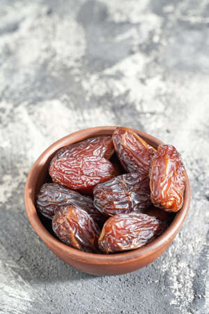 Bowl with dry dates. Top view heap. Healthy sweet snacks. Islamic turkish appetizer. Delicious fresh fruit. Bright background Standard-Bild