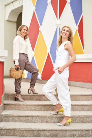 Pretty young women posing on stair. Happy female persons outdoors. Summer city business portrait. Blonde hair. Cute adult students at town. Standard-Bild