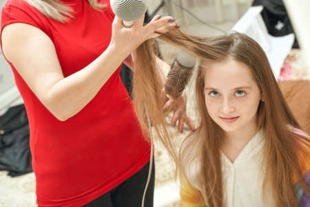 Mother dry daughter long hair. Home activity. New normal. Barber equipment. Lifestyle kid hairdress. Glamour master brush. Lockdown action. Pretty young girl Standard-Bild
