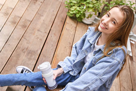 Pretty girl drink beverage outdoors. Buy takeaway coffee in own cup. Caucasian real people. Single female person. Alone. Ecology concept. Positive attractive human. Jeans dress. Sustainable lifestyle Standard-Bild